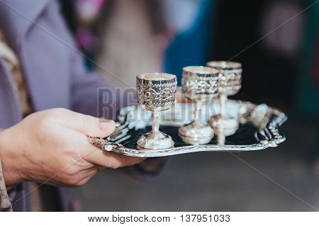 silver wine glasses on a silver plate. set of silver cups on a tray