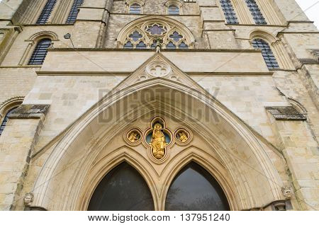 entrance of the Chichester cathedral. The Chichester Cathedral founded in the 11th century is dedicated to the Holy Trinity and contains a shrine to Saint Richard of Chichester.