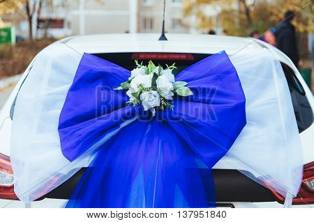 A black wedding car decorated with roses. Luxury wedding car decorated with flowers and ribbons.