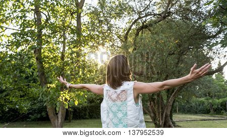 Young woman celebrating the morning sun and spring season as she stands outdoors in the garden at sunrise with outspread arms rear view.