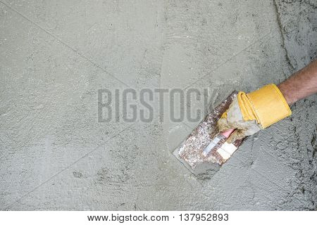 Workman or builder doing plastering of a concrete surface top view of his hand and tool in a DIY renovation and construction concept with copy space.