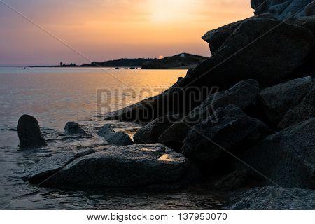 Sea rocks on a sandy beach at sunset, west coast of peninsula Sithonia, Chalkidiki, Greece