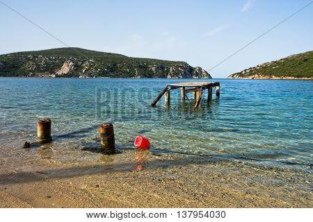 Old rusty wooden dock at sunny morning near the entrance to Porto Koufo harbor, Sithonia, Greece