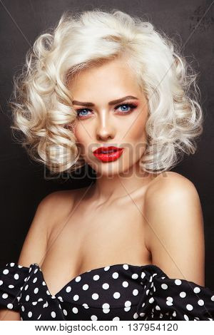 Vintage style portrait of young beautiful sexy blonde pin-up girl with curly hair and red lips over grunge background