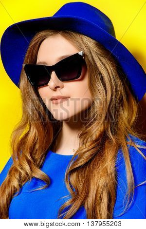 Dreamy summer girl. Smiling young woman in sunglasses over bright yellow background.