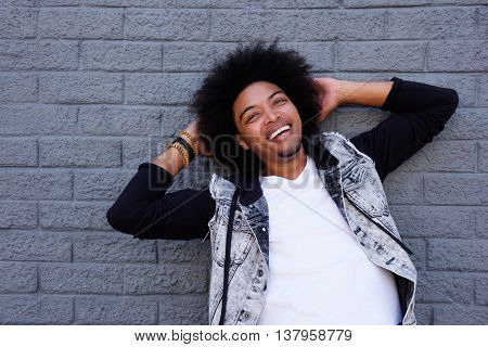 Cheerful Young Man Leaning Back Against Gray Wall