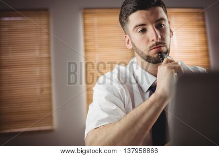 Thoughtful young man against window in office