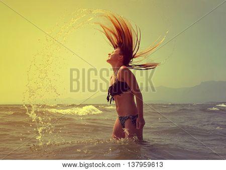 Beautiful girl in the water waving hair