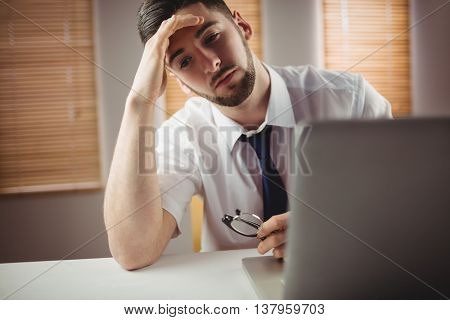 Tired young man sitting by desk in office