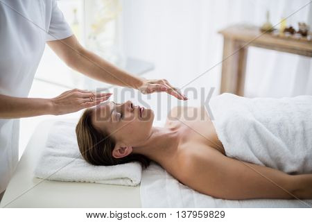 Midsection of therapist performing reiki on young woman at spa