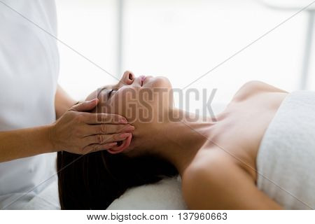 Young woman receiving massage from masseur at spa