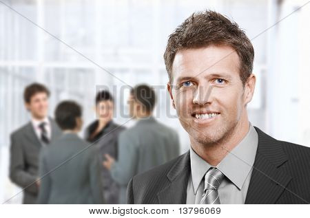 Smart businessman smiling at camera in closeup, colleagues talking in office lobby.