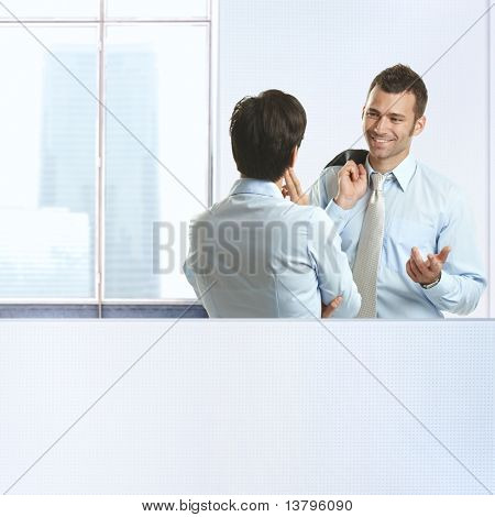 Two coworkers standing chatting in business office, smiling.