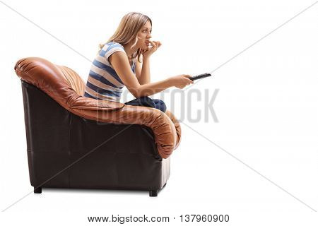 Young woman watching TV and biting her nails seated on an armchair isolated on white background