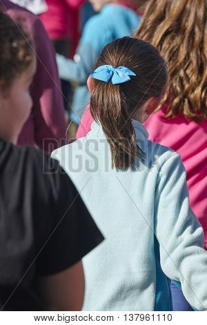Young girl with ponytail on her back. Outdoors. Vertical format