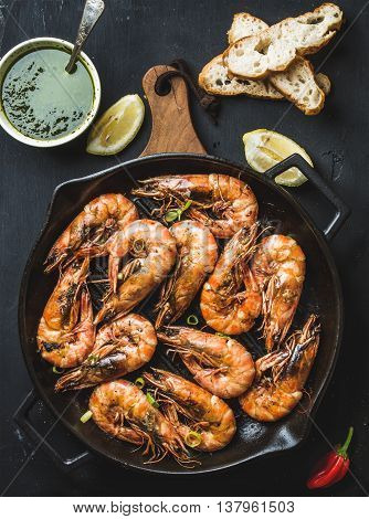 Roasted tiger prawns in iron grilling pan on wooden board with fresh leek, lemon slices, bread, pepper and pesto sauce over black background, top view, vertical composition