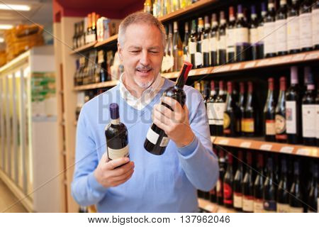 Man in a supermarket comparing two wine bottles