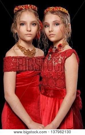 portrait of beautiful  little girls in red dresses  on black background