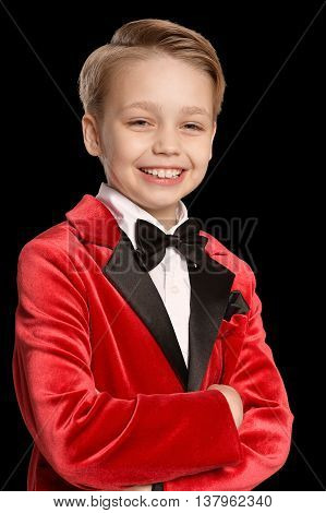 Handsome little boy in a tuxedo on black background