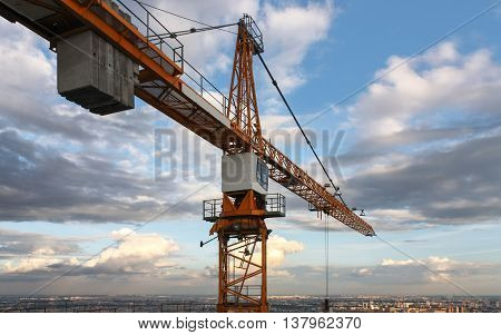 Industrial construction cranes against the backdrop of a cloudy sky