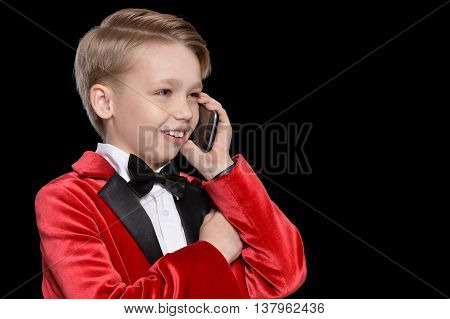 Handsome little boy in a tuxedo with mobile phone on black background