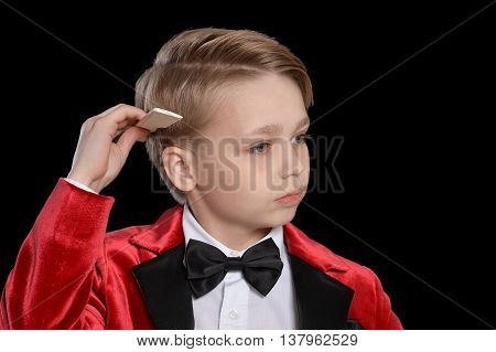 Handsome little boy in a tuxedo with comb on black background