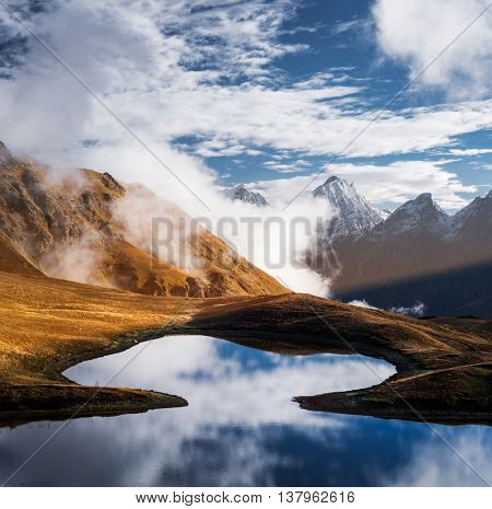 Highland Lake. Mountain landscape with tops and clouds. Reflection of the sky in water. Beauty in nature. Main Caucasian ridge. Koruldi lake, Zemo Svaneti, Georgia. Color toning