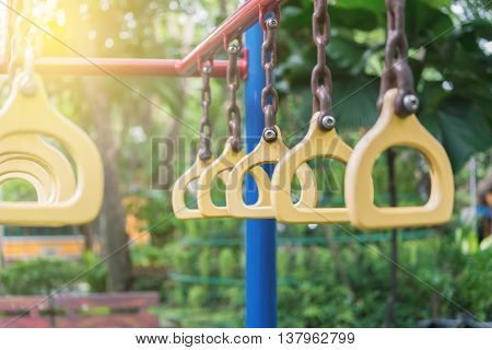 Close focus on hanging rings on the playing bar in green park with soft sunlight