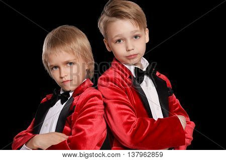 Handsome   little boys in a tuxedo on black background