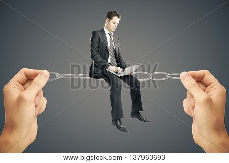 Balancing concept. Businessman miniature with laptop sitting on chain held by hands on dark background