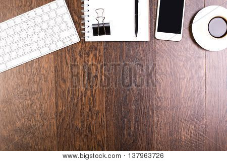 Top view of wooden desktop with keyboard spiral notepad other stationery items coffee cup and blank smartphone. Mock up