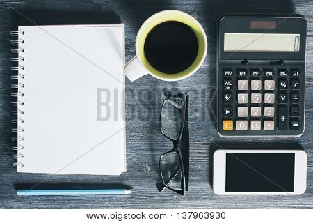 Top view of wooden office desktop with blank mobile phone spiral notepad coffee mug glasses blue pencil and calculator. Closeup Mock up