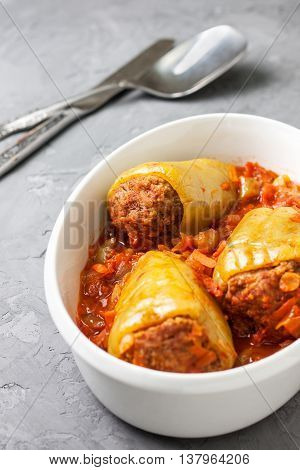 peppers stuffed with tomato sauce in a white dish for roasting on a concrete background