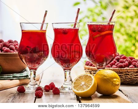 On wooden boards are ice cold beverage glasses with red raspberry lemon cocktail . Alcohol country cocktail beverage number hundred one with raspberry basket. Cocktail on outdoor.
