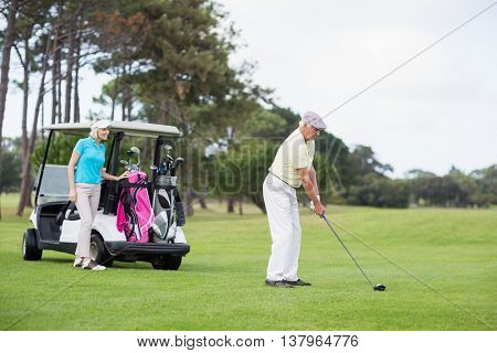Full length of golfer with woman standing by golf buggy