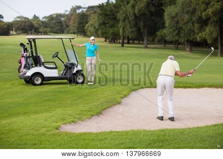 Mature golfer standing on sand trap by woman at golf course