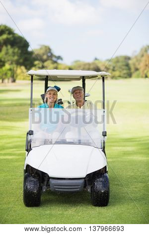 Portrait of happy golfer couple sitting in golf buggy