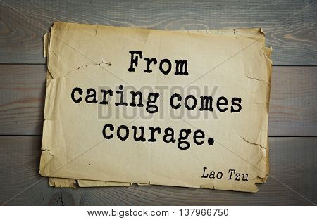 Ancient chinese philosopher Lao Tzu quote on old paper background.  From caring comes courage.