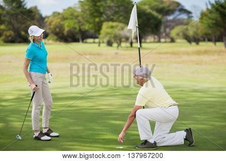 Full length of couple playing golf on field