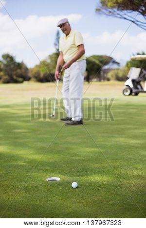 Full length of mature man playing golf while standing on field