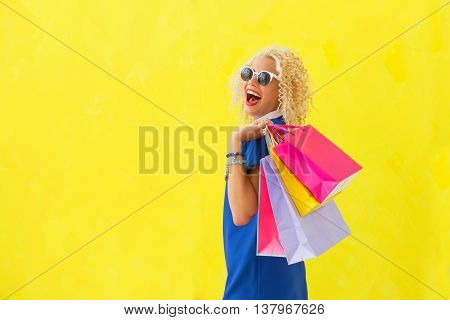 Funny woman holding shopping bags over her shoulder