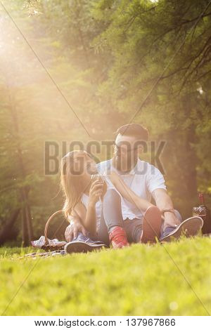 Couple in love sitting on a picnic blanket in a park talking to each other drinking wine and enjoying a beautiful peaceful day in nature