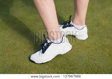 Low section of woman wearing sports shoes while standing on field