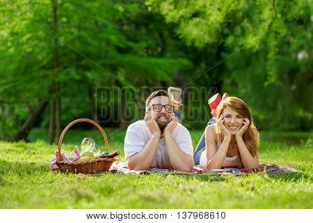 Couple lying on a picnic blanket in a park with a picnic basket filled with fruit food and wine placed next to them