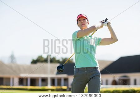 Low angle view of golfer woman taking shot while standing against clear sky