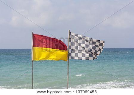 black and white checkered flag and surf lifesaving flag on beach photo