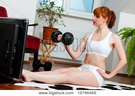 Woman is exercising with weights in her living room watching a fitness video