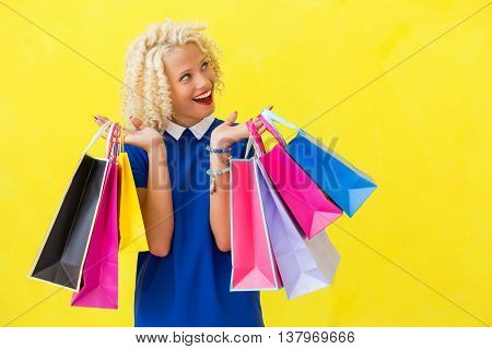 Excited woman with shopping bags looking up