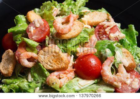 Caesar Salad with Shrimp on a black plate