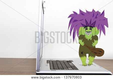 Internet troll standing on laptop on desktop.
